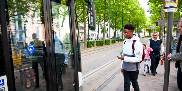 Enkele mensen wachten aan een tramhalte op de tram, die net aankomt.