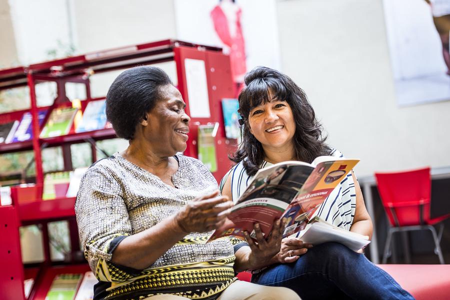 Rosario en een andere vrouw kijken in een kookboek.