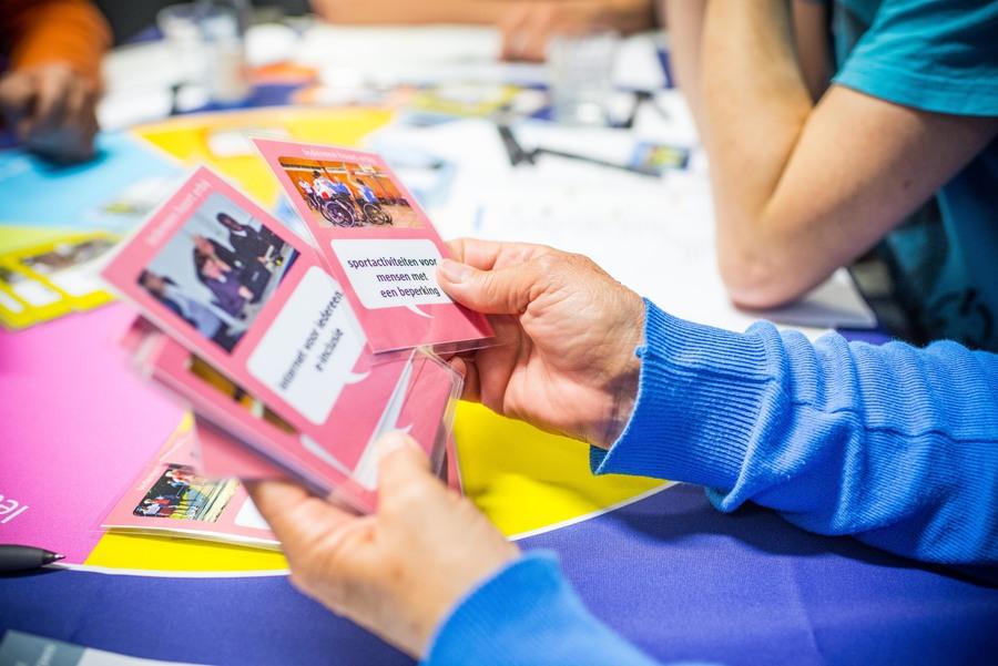 Man bekijkt kaartjes met thema's op startmoment burgerbegroting