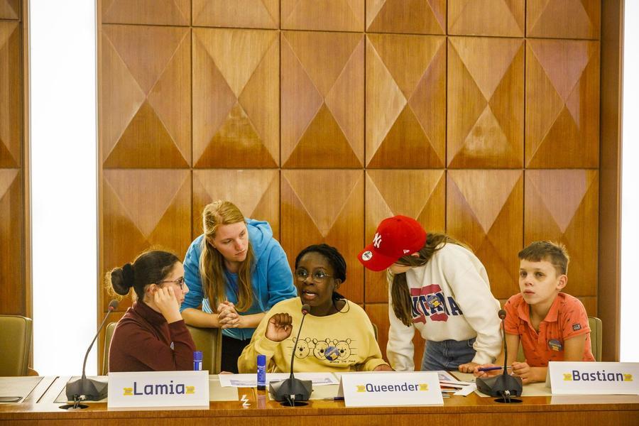 Vier leden en een begeleidster van het Junior Team aan het debatteren over wat ze belangrijk vinden in het district.