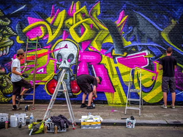 Streetart-artiesten zijn in de weer met spuitbussen op een muur.