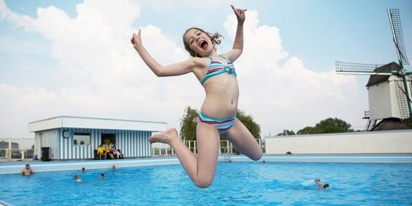 Meisje dat springt naast het openluchtzwembad De Molen