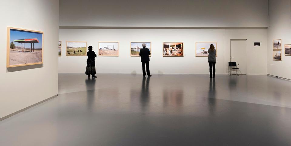 3 mensen kijken naar fotokunstwerken in het Fotomuseum.