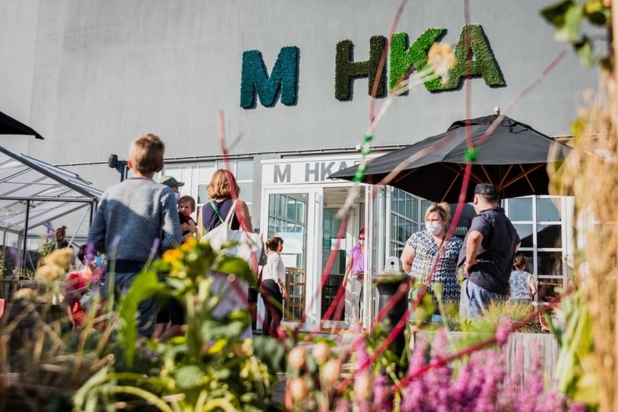 Terras, mensen en de letters M HKA in mos tegen de muur