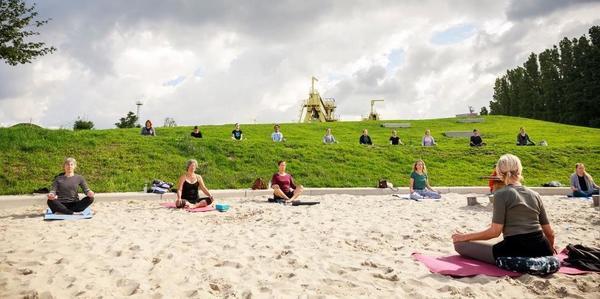 Mensen in yogahouding op Spoor Oost