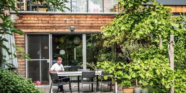 Man leest de krant op een terras in het groen. In de achtergrond is een gerenoveerde woning met veel glas en hout in de gevel te zien.