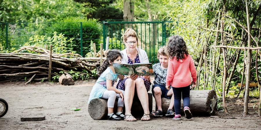 Leerkracht en kinderen zitten op een boomstam een boek te lezen