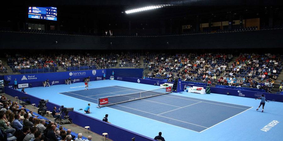 Indoor tennisterrein met 2 tennissers in actie en met publiek.