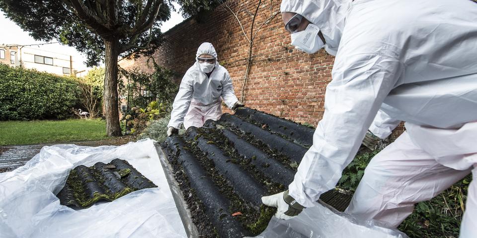 Twee mensen verwijderen een golfplaat in asbest. Zet voeren ze af in gespecialiseerde zakken en dragen witte beschermende kledij.