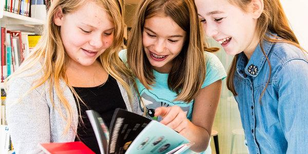 Drie meisjes op bezoek in de bib