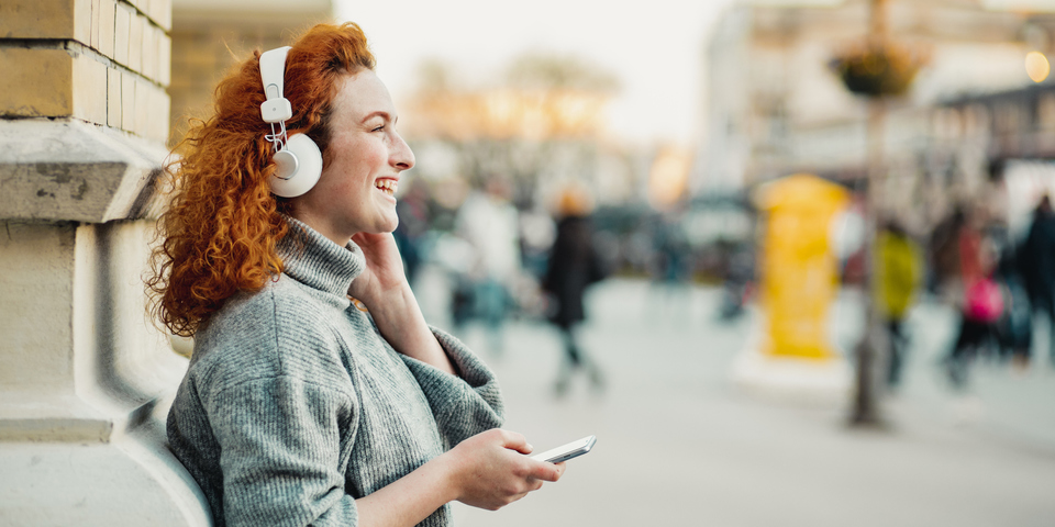 Dame met hoofdtelefoon luistert glimlachend naar iets dat ze via de smartphone afspeelt