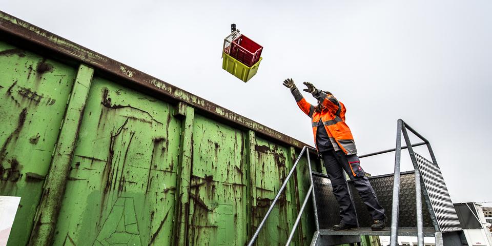 medewerker van het containerpark die iets weggooit
