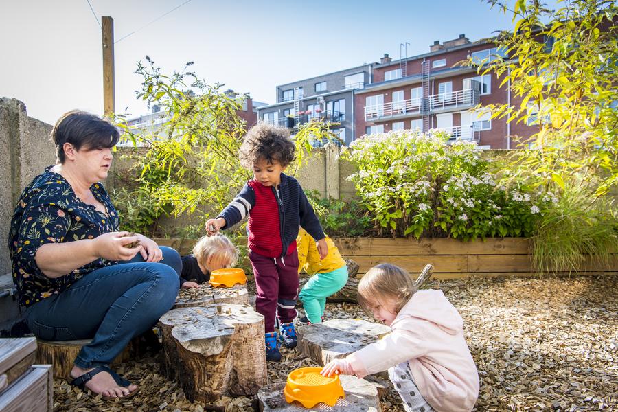Kinderen en begeleidster spelen in de houtsnipperzone