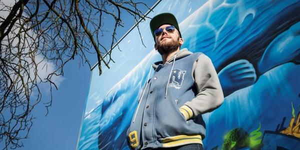 Yvon Tordoir voor de muurschildering aan zwembad Groenenhoek