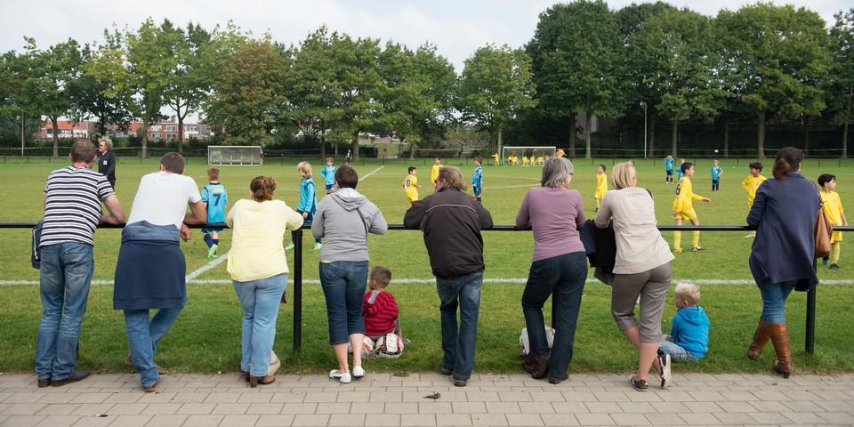 Ouders kijken naar voetbalmatch kinderen