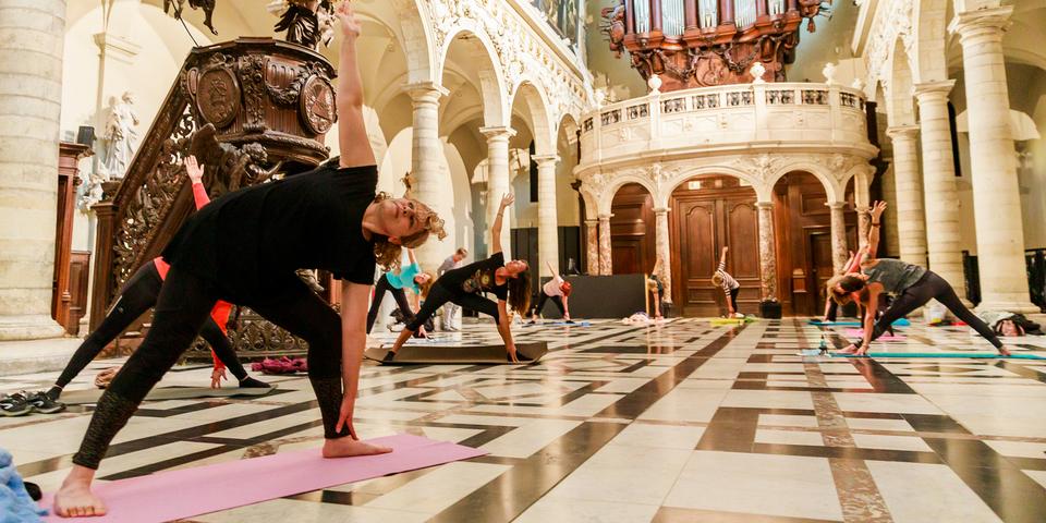 Een groep volwassenen doet yoga in Amuz (Antwerpen)