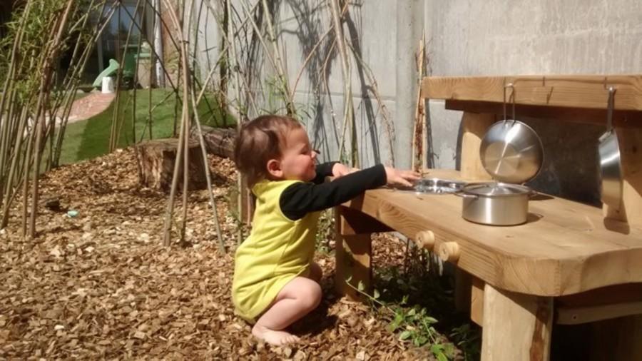 Meisje speelt in buitenkeuken