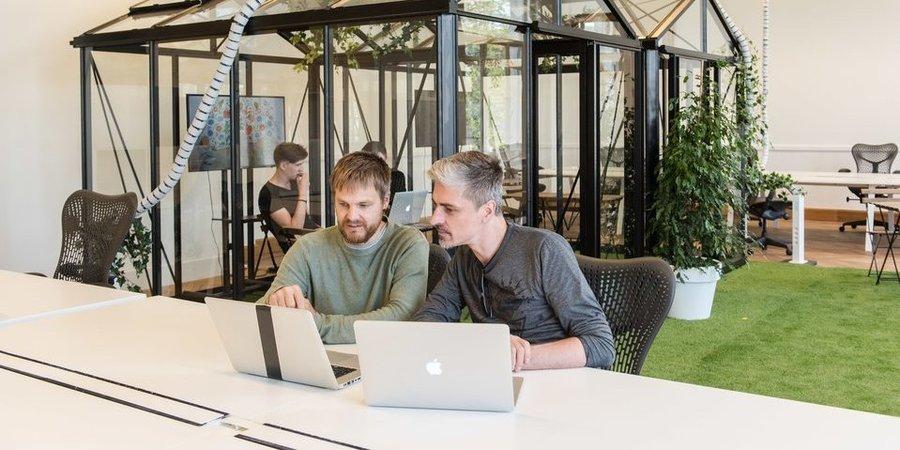 Twee mannen werken op een laptop aan een tafel in een groene kantoorruimte.