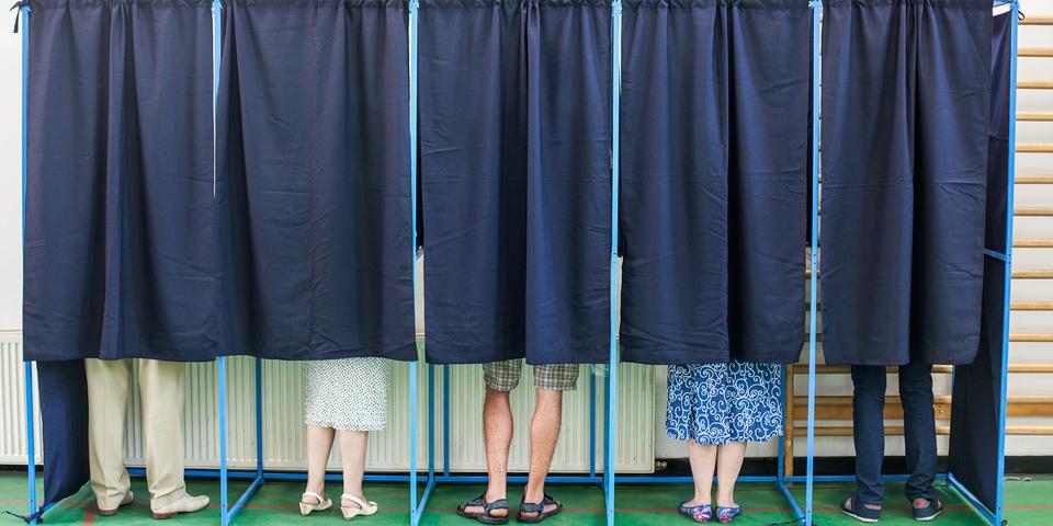 Mensen gaan met hun oproepingsbrief stemmen in stemhokjes tijdens de verkiezingen