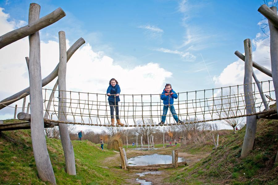 Een jongen en een meisje staan op een loopbrug over het speelterrein van het Park van Eden.