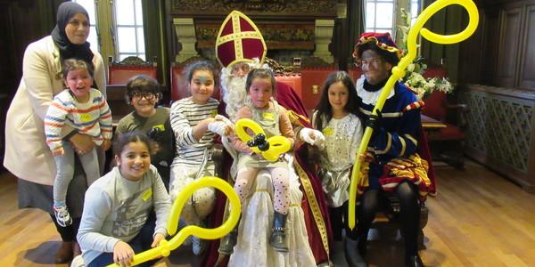 Kinderen gaan op de foto bij Sinterklaas.