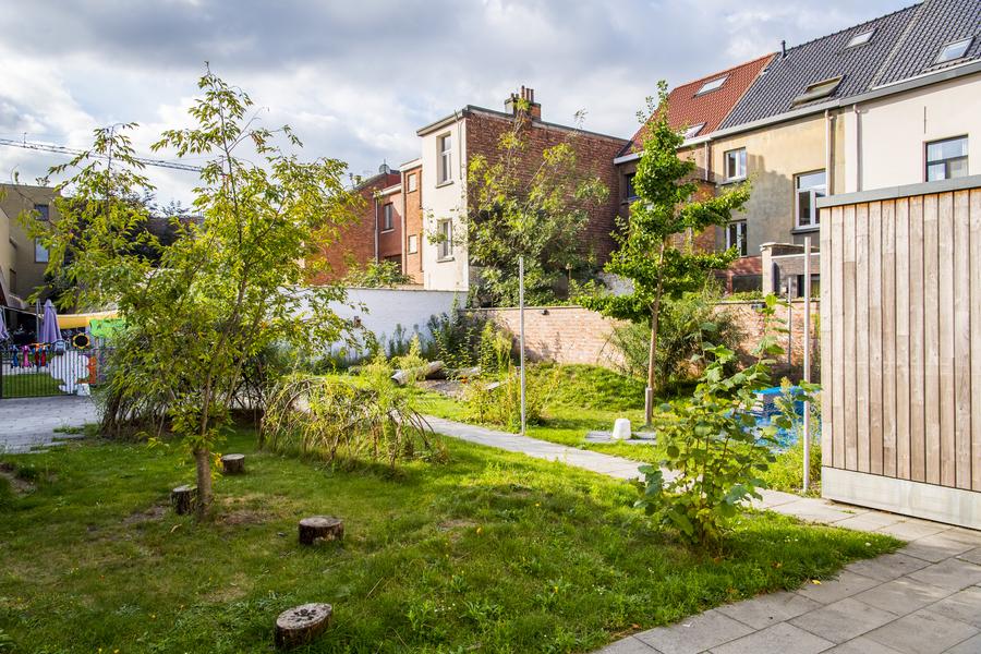 Een overzicht van de buitenruimte, met wilgenconstructies, heuveltjes, een zandzone, een houtsnipperzone en boomstammetjes