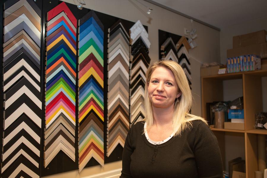 Dame poseert bij een muur van gekleurde lijsten