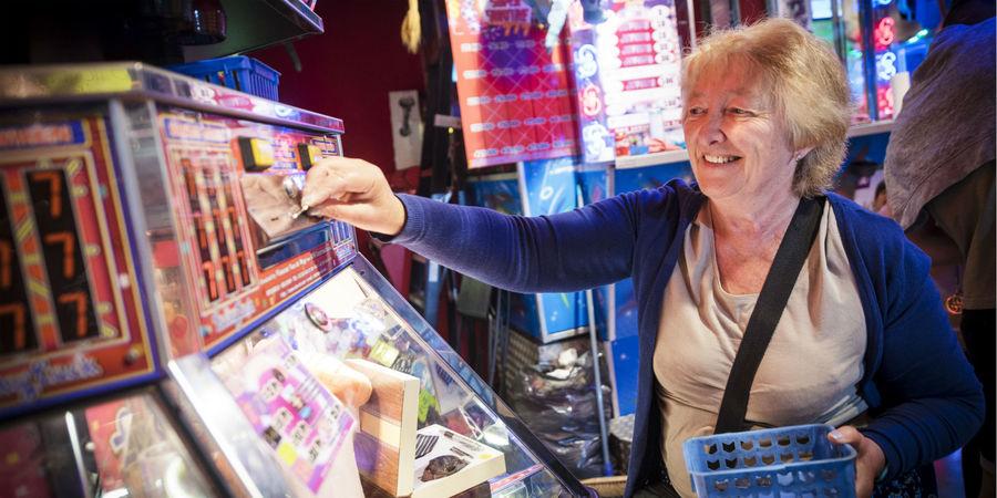 Vrouw gooit muntje in muntjesspel in lunapark