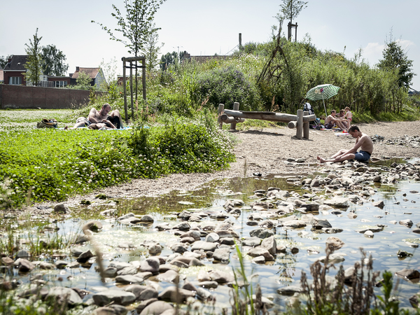 Mensen genieten van het goede weer aan de rand van het water
