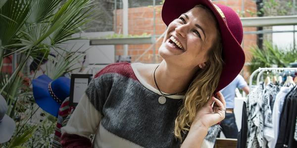 Vrouw lacht. Ze heeft een hoed aan.