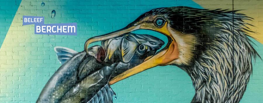 Graffitiwerk van een aalscholver die een vis opeet