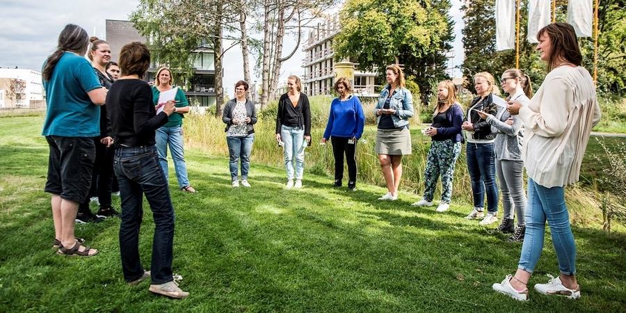 Een groep mensen staat in een kring om naar een opdracht te luisteren