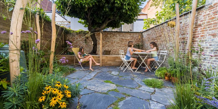Drie meisjes zitten in een tuin, op de voorgrond zien we planten en bloemen, op de achtergrond een houten platform en boom.