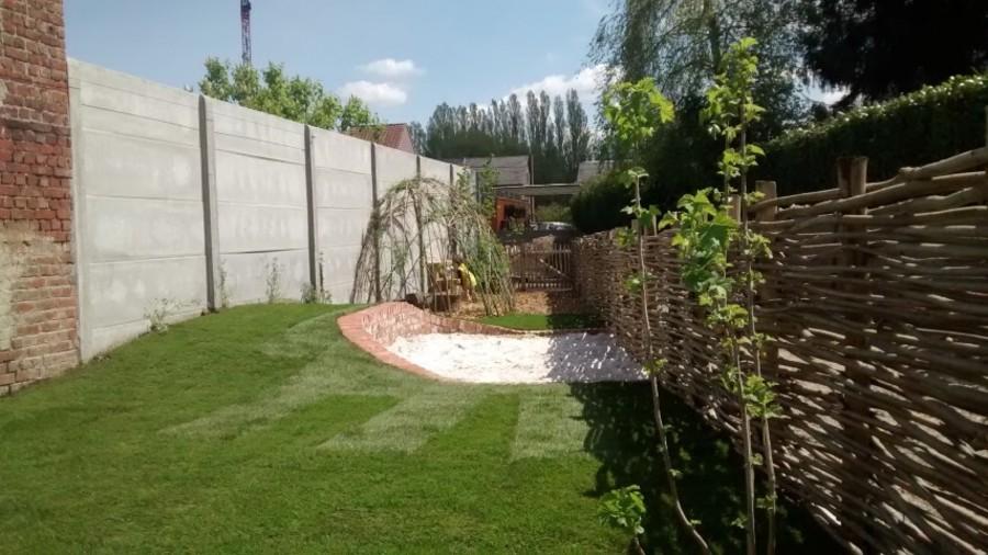 Een groen speelterrein met zandbak, gras, wilgenhut en keukentje op schors.
