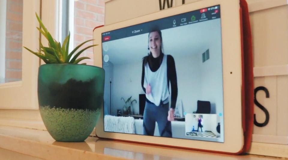 Een tablet op de vensterbank met op het scherm een vrouw die online sportles volgt