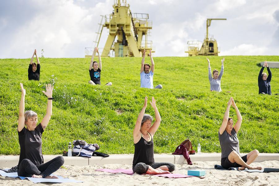 7 mensen nemen deel aan een openluchtles yoga