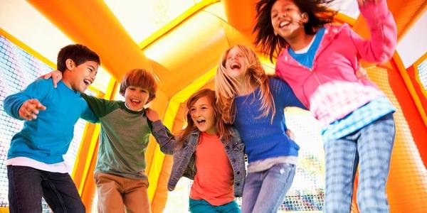Vijf kinderen maken plezier in een springkasteel.