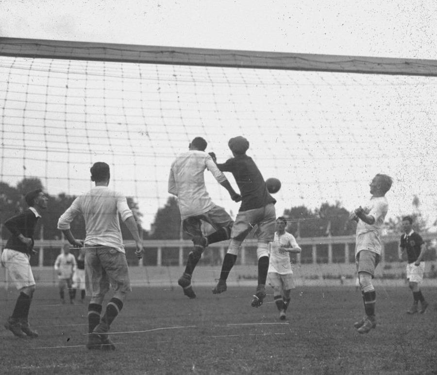 Sfeerbeeld voetbalmatch Olympische Spelen 1920: keeper en veldspeler springen naar bal