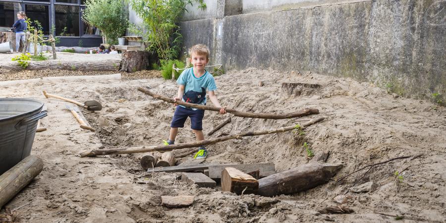 Een jongen bouwt een kamp met takken
