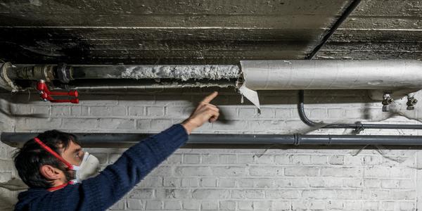 Een man draagt een mondmasker en wijst naar oude leidingisolatie met niet-hechtgebonden asbest.
