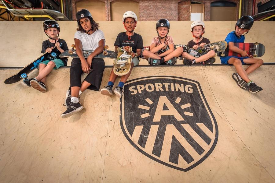Jonge skaters zitten op het nieuwe skatepark in de Parkloods van Park Spoor Noord.