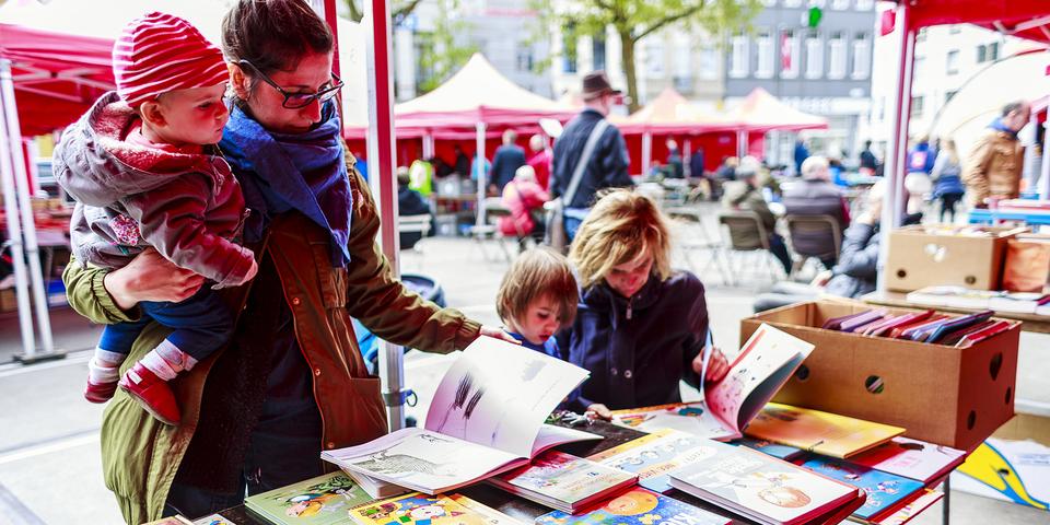 Bezoekers bladeren door de boeken op het De Coninckplein