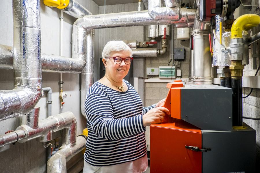 Vrouw toont de technische ruimte van het appartementsgebouw. We zien een moderne verwarmingsketel en geïsoleerde buizen.