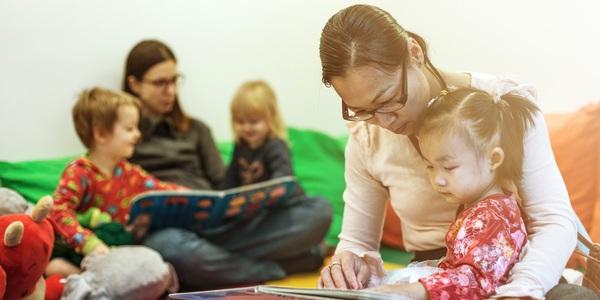 Moeders lezen samen met hun kinderen een boek.
