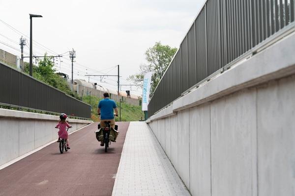 Vader en dochter fietsen de fietstunnel uit richting Bist.