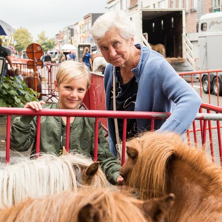 Een jongen en zijn grootmoeder strelen een paard.