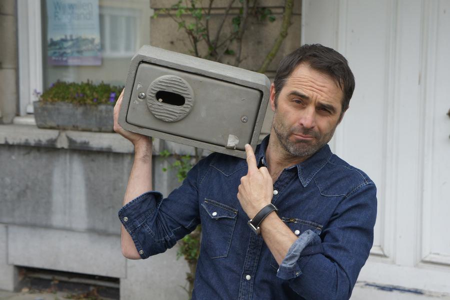 Michaël Pas, peter van het Natuurpuntproject, hangt een nestkast aan zijn woning.