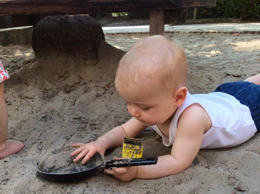 Baby speelt in zandbak
