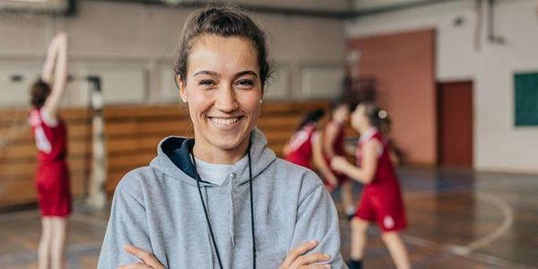 Vrouw in sportzaal met handballers op de achtergrond