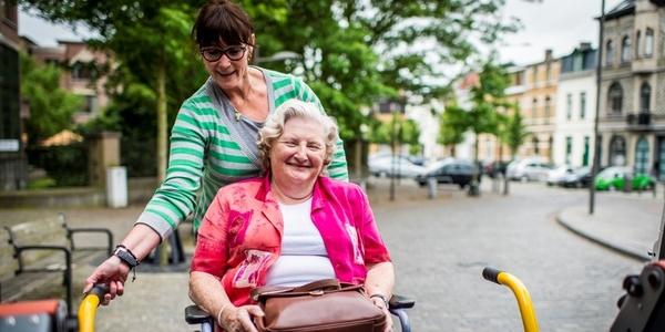 Een dame helpt een oudere dame in haar rolstoel in te stappen in een busje voor mindervaliden.